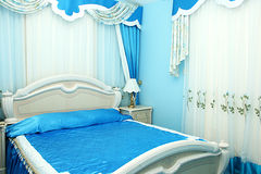 Bedroom. Luxurious blue  bedroom with beautiful curtains Stock Photos