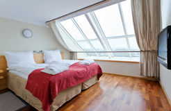 Bedroom. With wooden floor and big windows Royalty Free Stock Images