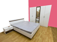 Bedroom. Modern bedroom with big wardrobe, bed with quality mattress, and two bedside cabinets on laminate floor Royalty Free Stock Image