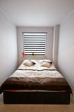 Bedroom. A sparse composition of a small bedroom with double bed and window with blinds Royalty Free Stock Photography