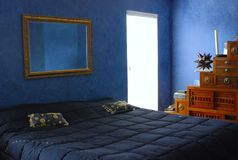 Bedroom. Here is a picture of a master bedroom that has nice decor with blue rag painted walls and a king size bed Royalty Free Stock Photography