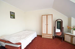 Bedroom. A loft bedroom neatly furnished with a single bed, cupboard and mirror. The door to the hall Stock Image