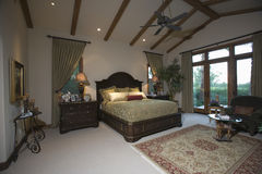 Bedroom With Beamed Ceiling And Patio Doors Royalty Free Stock Photos