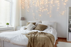 Bedroom with bed and christmas garland at home Stock Image