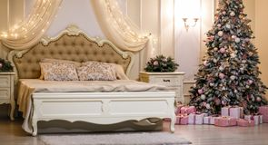 Bedroom with beige bed and Christmas tree. royalty free stock image