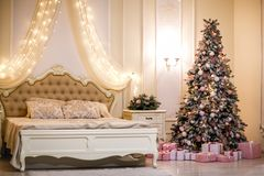 Bedroom with beige bed and Christmas tree. royalty free stock photo