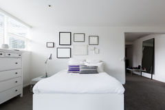 Bedroom with collection of blank frames on the wall Royalty Free Stock Image