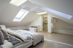 Bedroom connected with bathroom. In the attic Royalty Free Stock Photo