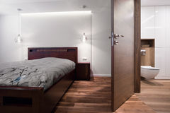 Bedroom connected with bathroom. In wooden house Royalty Free Stock Photography