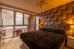 Bedroom with 3d wallpaper and big bed. Warm brown bedroom with 3d wallpaper, window and double bed royalty free stock image
