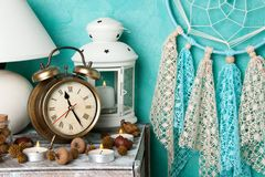 Bedroom decor on aquamarine. Blue beige dream catcher , alarm clock and aroma candles in bedroom interior on aquamarine textured background. Bedroom decor royalty free stock image