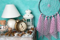 Bedroom decor on aquamarine. Pink gray dream catcher , alarm clock and aroma candles in bedroom interior on aquamarine textured background. Bedroom decor royalty free stock image