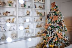 The bedroom decorated for Christmas. Cozy home interior. New year decoration. White room with large bookshelves. Christmas tree with shyning garland Royalty Free Stock Photo