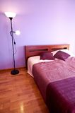 Bedroom decorated in violet colors Stock Photos