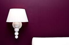 Lamp and purple wall. Bedroom decoration detail with a white lamp and a part of leather headboard Royalty Free Stock Photography