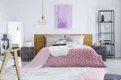 Bedroom designed for model. Stylish bedroom designed for a model with fashion poster and comfortable pink bed with wooden bedhead royalty free stock photos