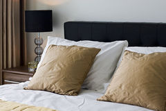 Bedroom detail. Pile of coshions and bedside table with lamp Royalty Free Stock Photography