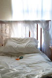 Bedroom detail simple with sunlight and healing stones. A simple bedroom under ambient light from the window coming in through blue sheer curtains to light up royalty free stock photo