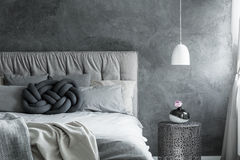 Bedroom with DIY knot cushion. Close-up of trendy minimalist bedroom with gray DIY knot cushion royalty free stock photography