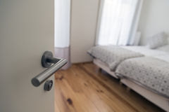Bedroom door. Door handle in focus. Door opens to show modern bedroom defocussed in background Stock Photography