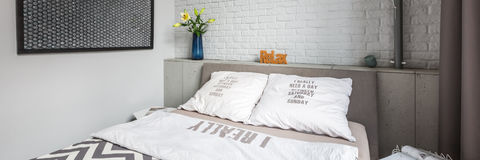 Bedroom with double bed. Modern bedroom with double bed and white brick wall, panorama royalty free stock photography