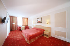 Bedroom with double bed with red linen, red armchairs Stock Photo