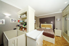 Bedroom with double bed, white baby cot. And closet with toys Stock Photography
