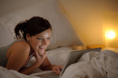 Bedroom evening - woman with laptop Royalty Free Stock Image