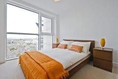 Bedroom with floor to ceiling windows. Bedroom with large floor to ceiling windows and orange decoration stock photo
