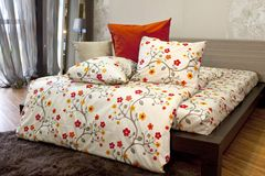 Bedroom with floral bedlinen. Details of the interior of a bedroom with Bedroom with floral bedlinen, wood bed royalty free stock photo