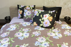 Bedroom with floral bedlinen. Details of the interior of a bedroom with Bedroom with floral bedlinen, wood bed stock image