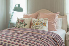Bedroom with flower pillows and pink striped blanket. Vintage bedroom interior with flower pillows and pink striped blanket on bed Stock Photos