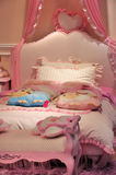 Bedroom for girl. Bed and beddings in bedroom in pink color for kids, with pillow and toys, shown as children's room interior and happy living environment Royalty Free Stock Photos