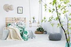 Bedroom with gray pouf. Plants, double bed, lamp and swing Royalty Free Stock Photo