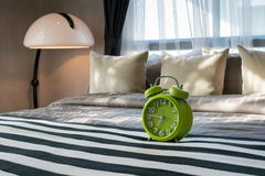 Bedroom with green alarm clock Royalty Free Stock Images