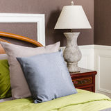 Bedroom with grey lamp on wooden nightstand Royalty Free Stock Images