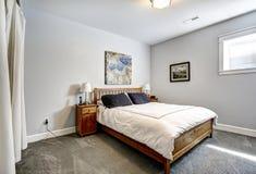 Bedroom in grey tones with wooden bed Stock Photo