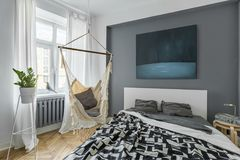 Bedroom with hammock. Nordic bedroom with double bed, hammock and modern painting stock photography