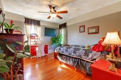 Bedroom with hardwood floor and grey walls. Stock Image