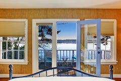 Bedroom with hardwood floor and opened door to walkout deck. Craftsman bedroom interior with hardwood floor and opened door to walkout deck. Northwest, USA royalty free stock photo
