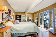 Bedroom with hardwood floor and opened door to walkout deck. Craftsman bedroom interior with hardwood floor and opened door to walkout deck. Northwest, USA royalty free stock images