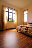 Bedroom with Hardwood Flooring. Bedroom interior with hardwood / wooden flooring and windows with curtain royalty free stock photo