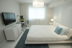 Bedroom with a HD television. Interior image of a bedroom with a flat screen HD tv hanging on the wall Stock Photos