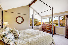 Bedroom with high iron frame bed. And vaulted ceiling Royalty Free Stock Photos