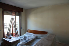 Bedroom of the house during painting of the walls with covered f Stock Images