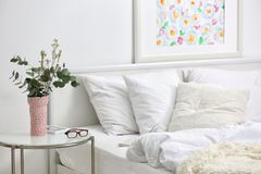 Bedroom interior with bed and flowers. On nightstand stock photos
