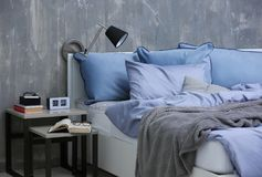 Bedroom interior with bed and nightstand. On grungy wall background Stock Photo
