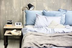 Bedroom interior with bed and nightstand. On grungy wall background Stock Images