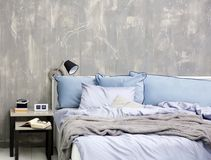 Bedroom interior with bed and nightstand. On grungy wall background Stock Photography