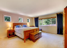 Bedroom interior with beige carpet floor and dark blue curtains. Royalty Free Stock Image